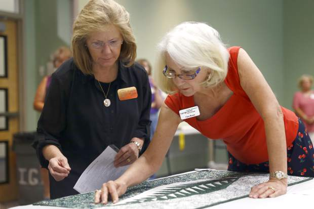 Quilt competition judges Pamela Walsh, left, and Chris Brown examine a quilt during Open Class Quilt Judging at the 98th Annual Weld County Fair at Island Grove Event Center, in Greeley.