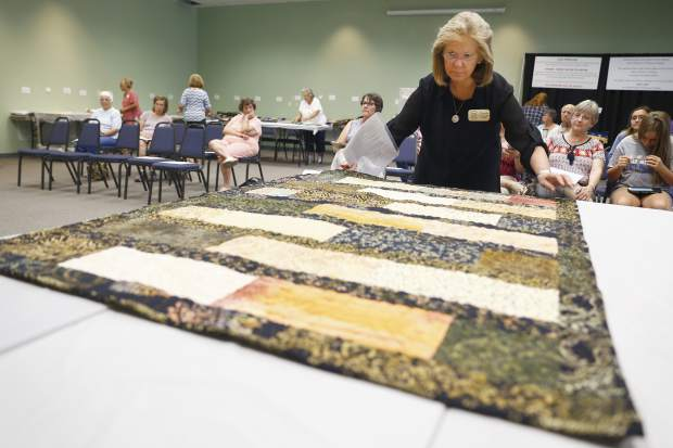 Quilt Competition judge Pamela Walsh examines a quilt during Open Class Quilt Judging at the 98th Annual Weld County Fair at Island Grove Event Center, in Greeley.