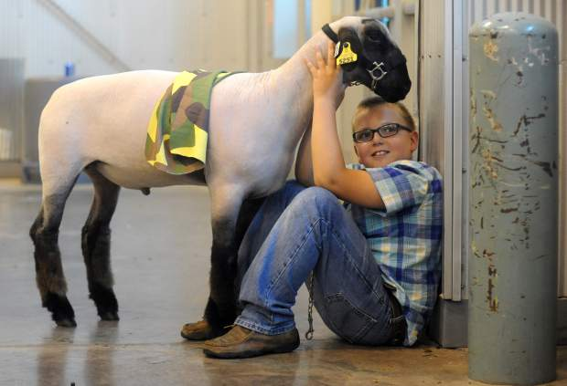 T.J Rumsey, 10, smiles as he sits with his sheep before competing on Thursday at the Market Sheep Competition during the Weld County Fair in the Island Grove Events Center in Greeley.