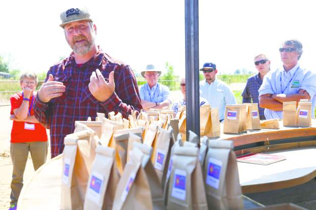 Director of Agronomy of Colorado Cultivars, Damian Farris, speaks to a group of almost 100 guests, who were on the Greeley Chamber's annual Ag Tour, at the Galeton hemp farm. Farris was talking about the struggles about the emerging hemp industry in Colorado.
