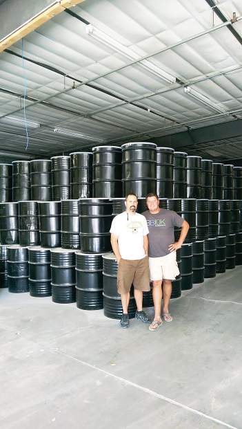 Scott Rice and Mike Lordemann stand in front of barrels of honey that are brought in from all over the Western United States. Rice said the company plans to produce 100 gallons of honey over the next 12 months.