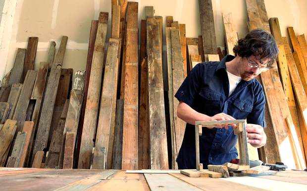 Ryan Channin works on a small basket as rows of salvaged wood stand behind him at his business Story Barns, 1120, 6th Ave., in Greeley. The wood used in Ryan's various projects is salvaged from old barns and repurposed into furniture and decorations.