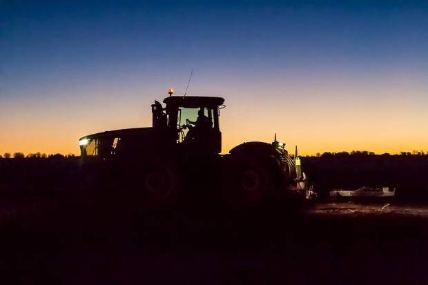 In the pre-dawn light, it becomes easier to see the Schnorr Farms massive 4WD John Deere 9410R tractor as it rises above the distant trees and is silhouetted against the sky. The tractor pulls semi-trucks through muddy fields while they are being loaded by the digger.