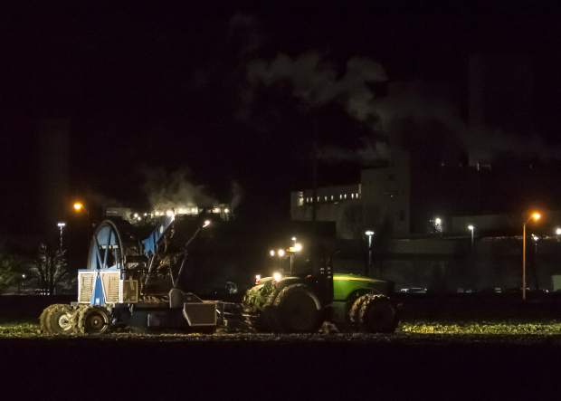 The tractor and the Red River digger are in a pool of light from the huge tractor coming from behind. The Budweiser plant is in the background. It is 3am and the harvest team is just one hour into its fourteen hour day.