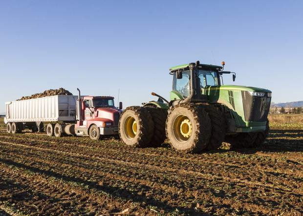The John Deere 9410R dwarfs the semi that it is pulling. The truck has to match its speed to the digger as it is being loaded, and in a muddy field the truck is not up to the task, so the tractor tows the semi. The muddy field and the 25 tons of beets are no match for the 4WD 13.5L 6-cyl diesel which develops 451 hp.