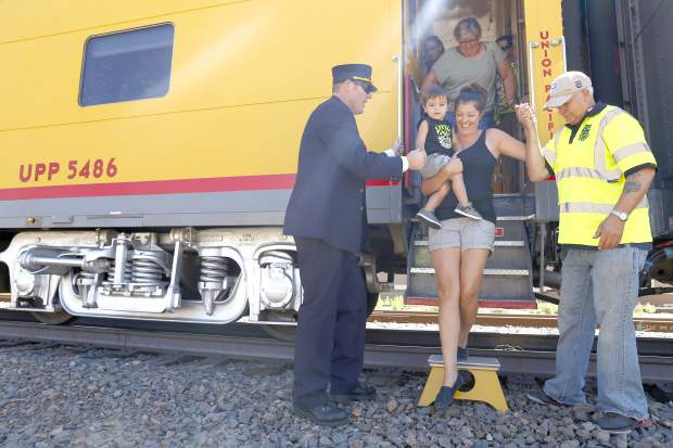 Conductor Bryce Allen and Dean Anderson help Helen Tapia and her son Cayden, 2, exit The Denver Post Cheyenne Frontier Days train pulled by Union Pacific's No. 844 steam locomotive Thursday morning at The Greeley Train Depot.