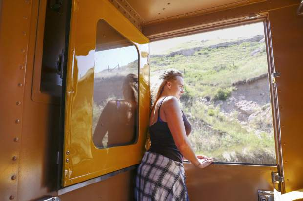 Tatjana Scherschel ,19, leans out the window Thursday morning on The Denver Post Cheyenne Frontier Days train. The historic steam locomotive will make several runs from Cheyenne to Denver with a stop in Greeley this weekend.
