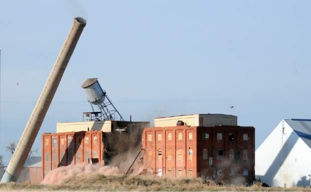The chimney, water tower, and central support walls of the former Great Western Sugar Factory begin to fall during the demolition as the charges are detonated in Eaton in 2013.