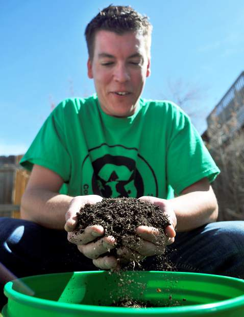 A handful of compost slips through Jeff Schmidt's fingers as he shows off some of the finished product his composting company created on Tuesday at his greenhouse in Greeley. Schmidt, a University of Northern Colorado senior, got the idea for his business during a class.