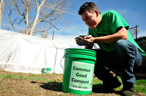 Jeff Schmidt leans in to smell his compost as he crouches over a bucket of the finished product on Tuesday at his greenhouse in Greeley. Schmidt launched Common Good Compost in Greeley in February.