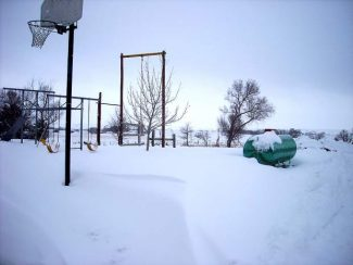 The drifts north of our house were fairly even right up to the bottom of the swing seats. The watermelon propane tank reminds us that summer is coming.