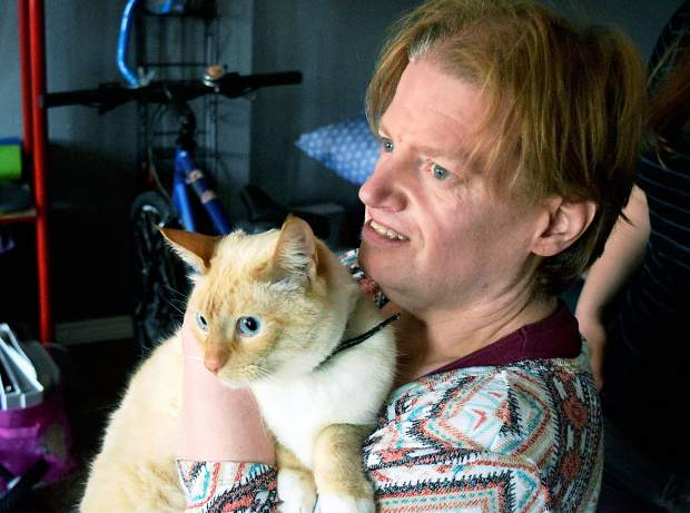 Dana Hoff snuggles with snowflake, her cat, in her guest house in the backyard of the home of Michelle Rice and Nicole Nelson in Eaton.