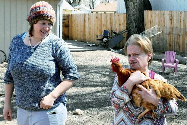 Dana Hoff, right, snuggles with Shirley, a friendly chicken, while Nicole Nelson watches in their Eaton backyard. Hoff came to live with Nelson and Michelle Rice, close friends and roommates, as a part of her time with Envision. She has since lost 120 pounds and is happier.