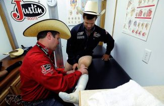 Dr. Jason Stoneback, left, checks out the leg of saddle bronc rider Heith DeMoss while inside the Justin Boots Sportmedicine Team trailer outside of the Stampede Arena on Sunday. Stoneback is a former rodeo competitor who volunteers his time to help out other rodeo cowboys.