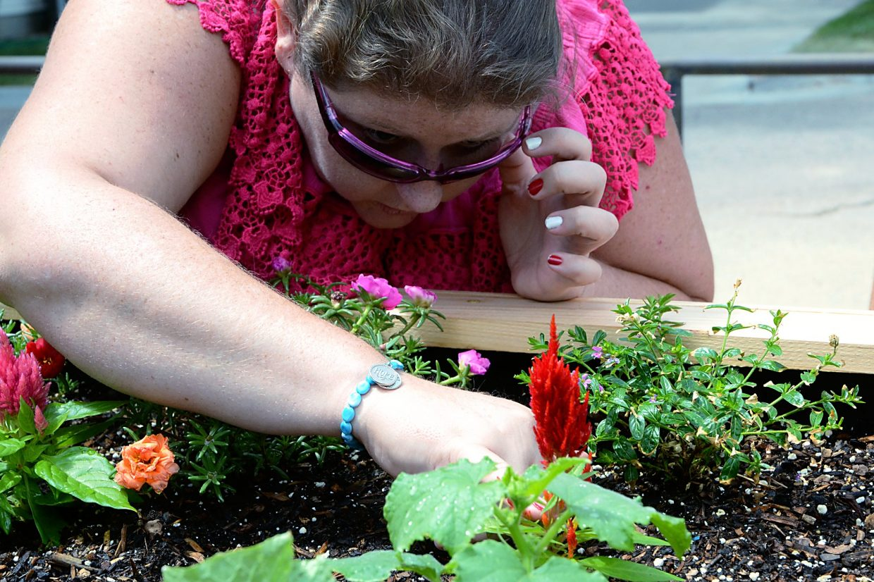 """Christina Morris, wearing a bracelet that says """"Hope,"""" peers at a garden at Stephens Farm Brain Injury Campus, where she lives in Greeley."""