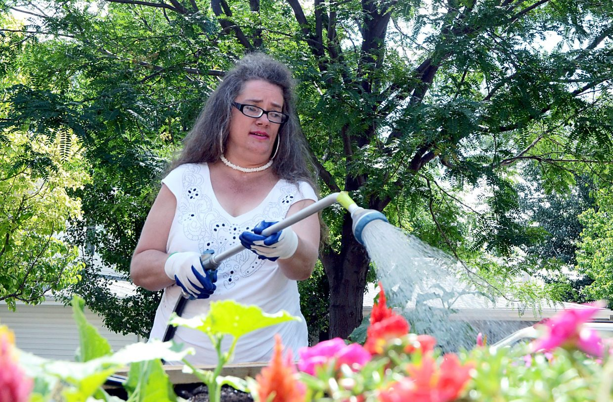 Deanna VanWagner waters some flowers in a planter on the Stephens Farm Brain Injury Campus in Greeley. VanWagner wanted a garden for years and finally got one thanks to a grant from Lowes.