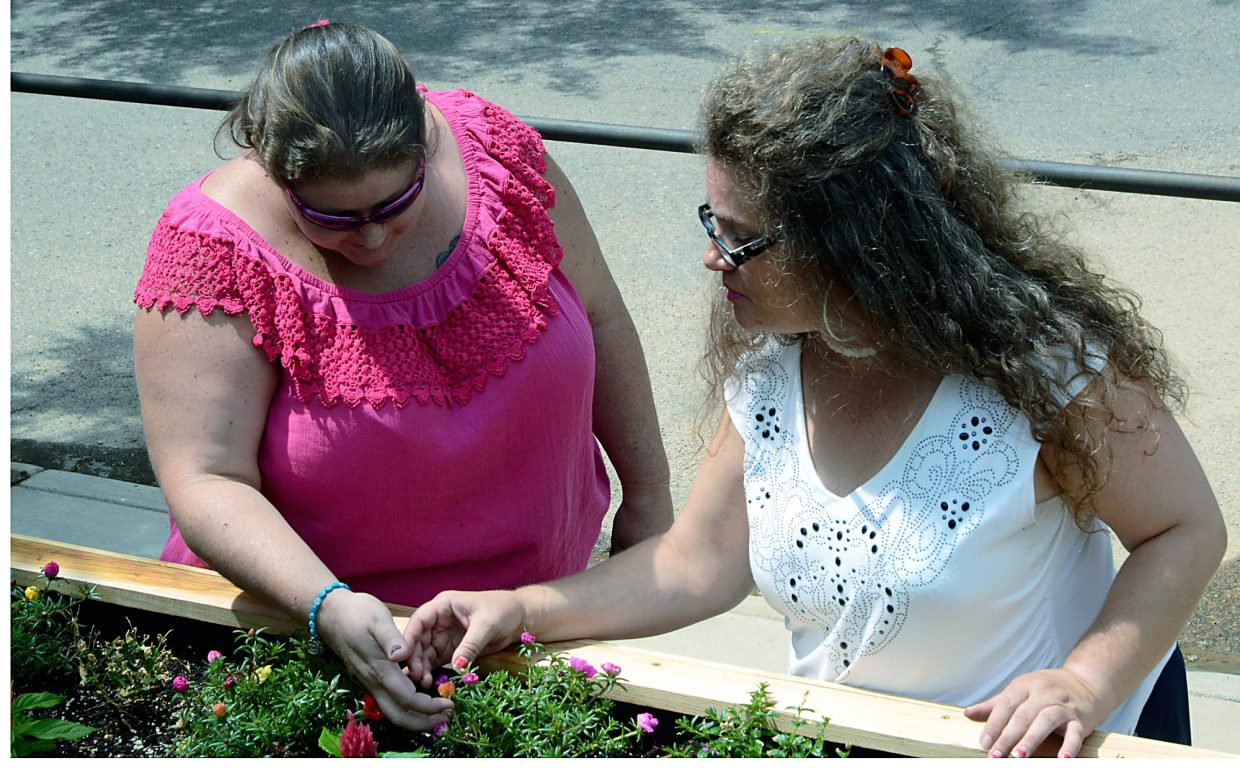 Deanna VanWagner and Christina Morris look over the garden that they worked hard to plant and care for at the Stephens Farm Brain Injury Campus in Greeley.