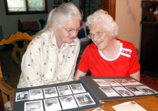 Leny Nerland (lt) and Wilma Boyd Lovell look over old photos at Wilma's home on their last get together in Cedar Rapids, Neb.