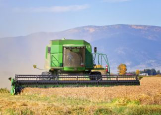 Jim Meadows and his 9650 John Deere combine rush to harvest his wheat before the weather changes and winter comes to the San Luis Valley in southern Colorado.