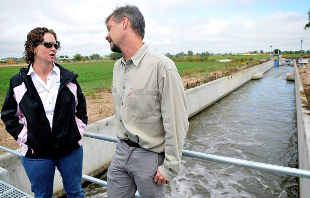 Amy Johnson, with Northern Colorado Water Conservation District, talks with Kevin Houck, Colorado Water Conservation Board, on Wednesday at the unveiling of a water control system near Platteville.
