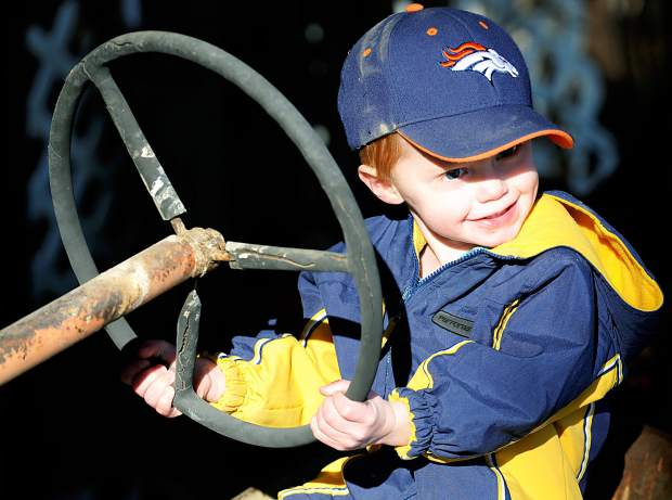 Archer Goetzel, 1, plays on a old 1940s tractor while on the family farm near Windsor on Monday. The family has farmed the area for 144 years.