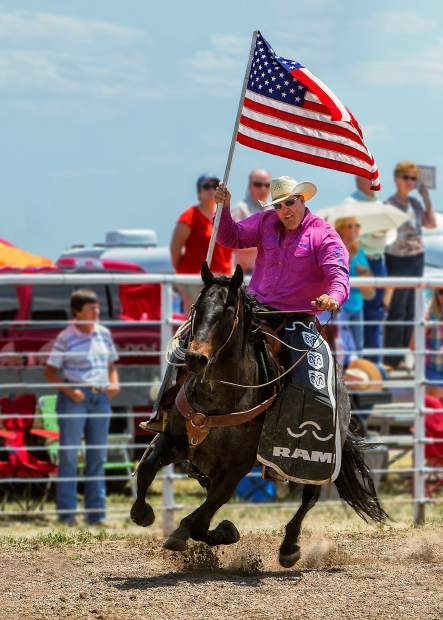 Pickup man Matt Carroll posts the colors at the 93rd Earl Anderson Memorial Rodeo held in Grover, Colorado. The rodeo at Grover is a Father's Day tradition and Carroll has been working it for ten years.