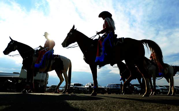 The Stampede Riders are silouetted against the clearing sky Wednesday afternoon at the start of the daily parade at the Greeley Stampede in Island Grove Regional Park. The parade which show cases the Stampede riders, as well as the iconic longhorns, starts at 6 p.m. every day in the park.