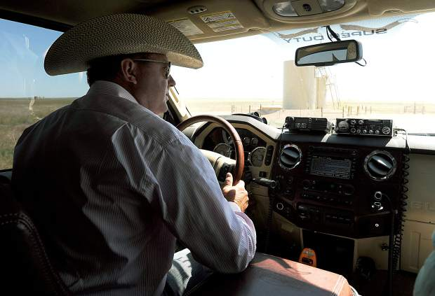 Art Guttersen drives on his family's land as he checks his cattle and the oil/gas sites. Guttersen has over 500 wells sites on their land, and hopes his ranch can be a showplace for cooperation and innovation.