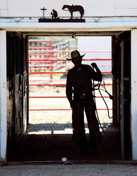 Ranch hand Ty Fenster walks out of a barn as he saddles up horses on the Guttersen family ranch near Kersey.