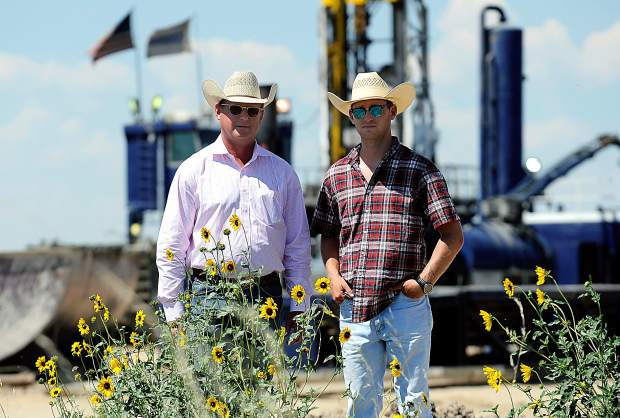 Art Guttersen, left, and his son, Parker Guttersen, 25, stand in front of one of the many oil/gas drilling sites located on their family's ranch. Guttersen works with oil companies on site locations of all equipment to ensure the most efficient use of the land.