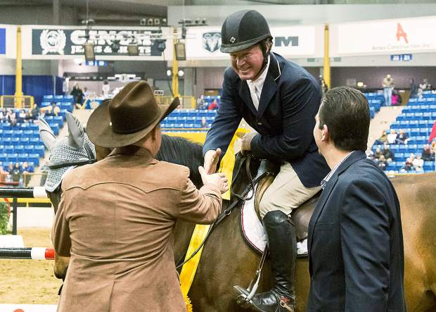 Paul Andrews (left) President and CEO of the NWSS, and Craig Pleva (right) General Manager of the Monarch Casino in Blackhawk, Colorado, congratulate John McConnell of Colorado for his 840 point run and Third Place on La Belle Soiree at the Monarch Casino Gambler's Choice Jumper Stake during the 110th NWSS.