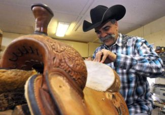 Mark Fellini smiles as he works on a saddle on Feb. 24, 2014 at the Old West Leather and Beads Company, 102 18th St, in Greeley, Colo. Fellini has operated Old West Leather and Beads for 26 years but will now be closing so he can pursue being operations pastor at the Northern Colorado Cowboy Church in Lucerne. (AP PHOTO/Joshua Polson/The Greeley Tribune)