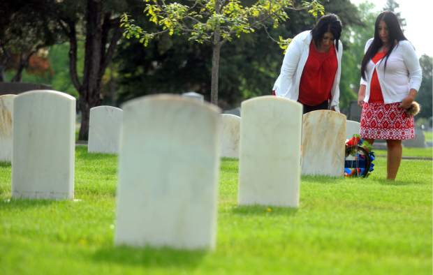 Rebecca Cruz, left, and Audrey Moreno stand in front of their father's grave stone Thursday at Linn Grove Cemetery in Greeley.