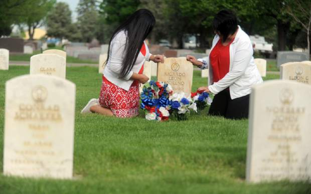 Audrey Moreno, left, and Rebecca Cruz finish decorating the grave stone of their fathers on Thursday at Linn Grove Cemetery in Greeley.