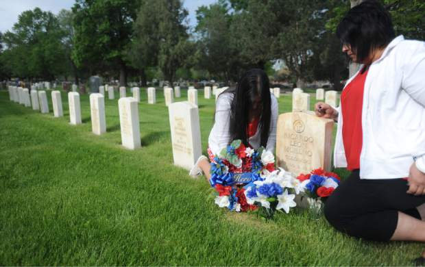 Audrey Moreno, left, and Rebecca Cruz decorate the grave stone of their father, Ricardo Moreno, on Thursday at Linn Grove Cemetery in Greeley. Ricardo was killed in Vietnam, the first soldier from Greeley killed in that war.