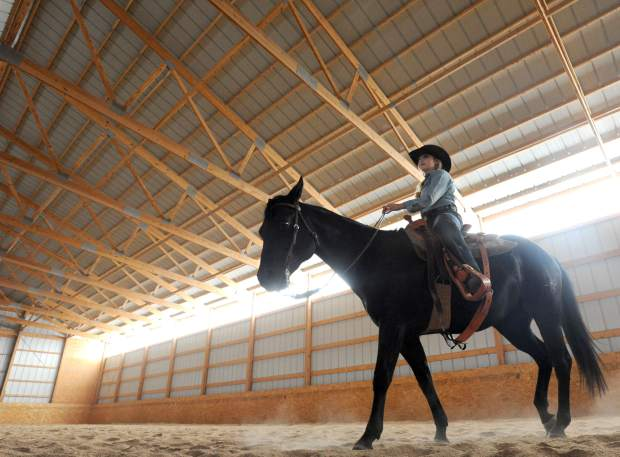Sweets the horse walks calmly around the arena with Kelsie Winslow on Monday at horse boarding facility outside Pierce.