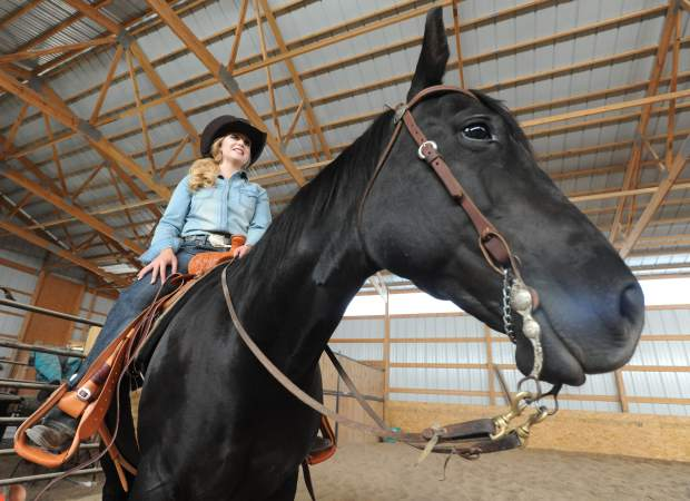 Kelsie Winslow sits in the saddle as she prepares to ride around the arena on Monday at a horse boarding facility outside of  Pierce.