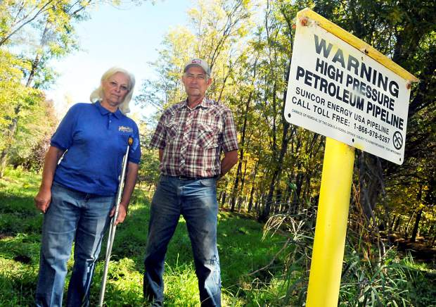 Gene and Jan Kammerzell stand along side a gas line marker inside their tree nursery, Arborland Nursery outside of Milliken. The oil and gas company, Suncor, pulled out thousands of dollars worth of trees on the property before the Kammerzell family took them to court. The jury found in favor of Kammerzell.