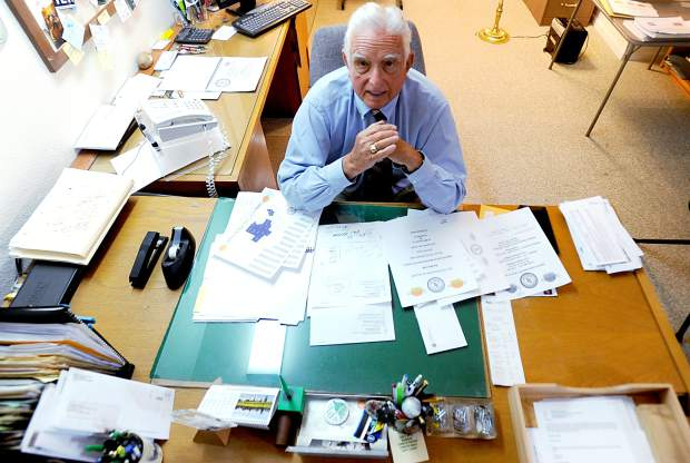 Dean Moore sits at a cluttered desk in his home office in Greeley. Moore has been working with the Market Watch program for 15 years.