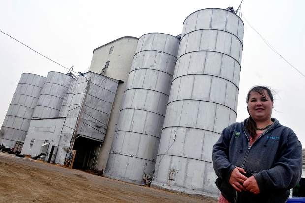 Rebecca Talmadge, stands out front of the four primary silos for S T Organics,  39580 Weld County Road 136 in Hereford. These silos are where the business hold its organic grains, however, they plan to move their grain storage to nearby silos in in Hereford.  S T Organics is one of few options to buy and sell certified, organic grain in the area.
