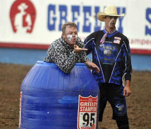 Justin Rumford, left, blows a kiss to a bull as he stands next to Brandon Loden during the Xtreme Bulls event at the Greeley Stampede last week at Island Grove Arena.