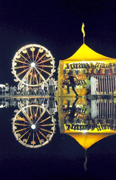 A puddle reflects the lights from the Greeley Stampede fair last year.