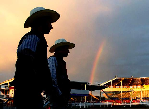 A rainbow crosses over the Stampede Arena as two cowboys are silhouetted by the clouds in the sky.