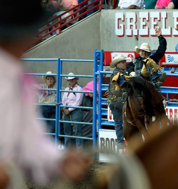 Blake Smith squeezes his eyes shut as his bronc leaves the chute during the bareback riding event at the Greeley Stampede on Monday. Blake scored an 83 in his event. (For the Tribune/ Kelsey Brunner)