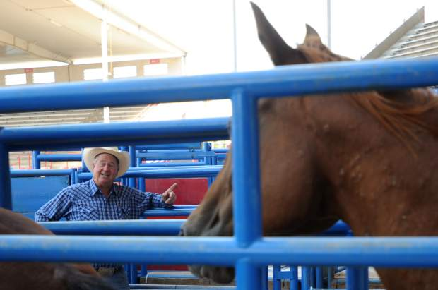 Bennie Beutler talks with a friend as horses shuffle past on Tuesday in the Greeley Stampede Arena.