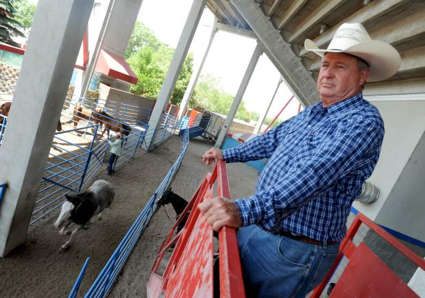 Bennie Beutler watches as horses are moved through the chutes in preparation for the rodeo Tuesday night at the Greeley Stampede Arena. Beutler has been providing the livestock, such as bulls and horses, since 1982.