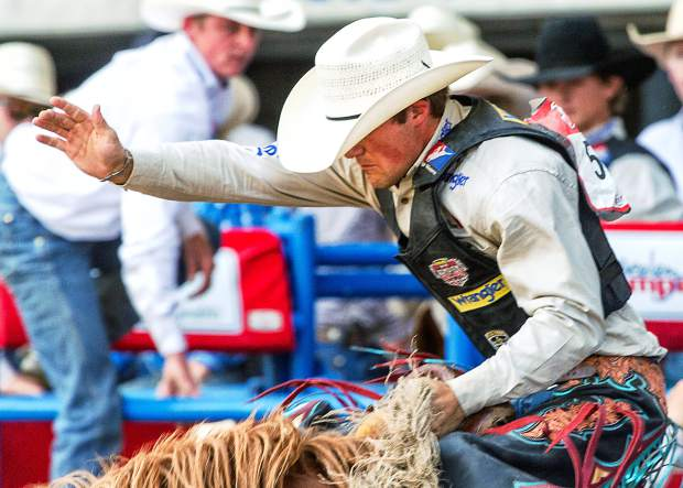 Saddle Bronc rider CoBurn Bradshaw of Beaver, Utah breaks out of the chute on Gingersnap to score an 85.0 at the 95th Greeley Stampede.