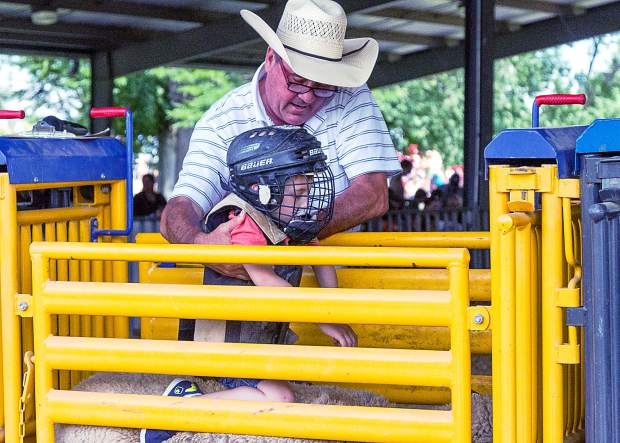 Kevin Rich of Wild West cattle Company has been a long-time proponent for introducing kids to rodeo with sheep riding. Rich gives last minute instructions to five year old Jayden Kropeg from Greeley, Colorado.