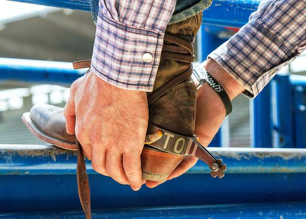 Back behind the chutes at the Greeley Stampede, the bronc riders are making final adjustments to their equipment and getting ready for their ride.
