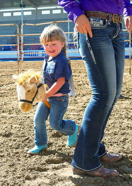 Three-year-old Edyta Rush is destined to be a barrel racer. She already has the tight turn around an obstacle mastered as she competes in the stick horse race at the Kids Rodeo during the Greeley Stampede.